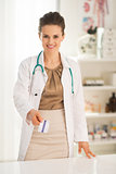 Happy medical doctor woman giving business card