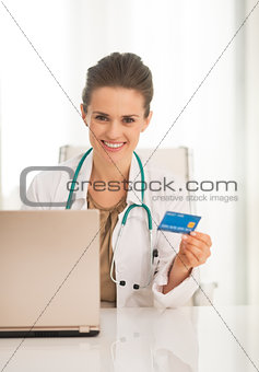 Portrait of happy medical doctor woman with credit card and lapt