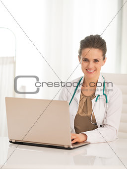 Portrait of happy medical doctor woman using laptop