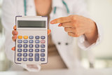 Closeup on medical doctor woman pointing on calculator