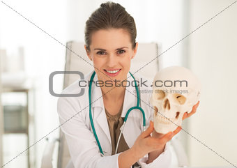 Portrait of happy medical doctor woman showing human skull