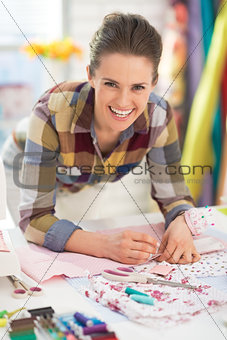 Portrait of happy seamstress working in studio