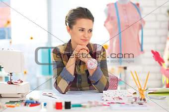 Portrait of thoughtful seamstress in studio