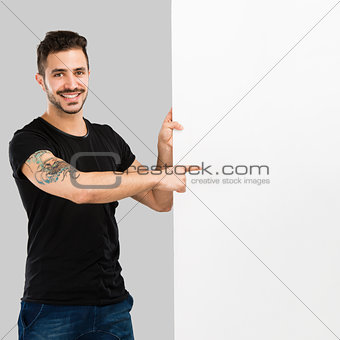 Latin man holding a blank billboard