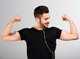 Man listen  music and looking his muscles