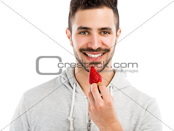 Happy young eating a strawberry