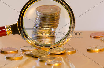 A stack of coins under a magnifying glass