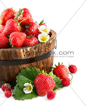 Fresh strawberry in wooden bucket with green leaf and flower