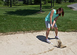 Woman swings at the golf ball caught in the sand trap