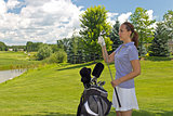 Golfing woman selects her club on the fairway
