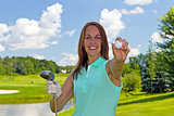 Woman with golf ball and club on the fairway