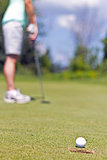 Woman sinking a putt on a golf green - selective focus