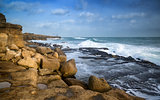 Landscape of waves crashing onto rocks during beautiful Winter's