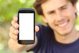 Happy man showing a blank mobile phone screen outdoor