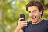 Happy man surprised looking at the smart phone