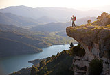 Hiker with baby relaxing on cliff and enjoying valley view. Siurana, Spain