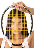 Young female tennis player looking through strings of racket over white