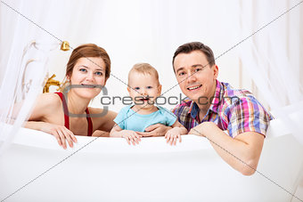 Happy couple with son sitting in bath