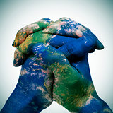 world map in the clasped hands of a man (Earth map furnished by