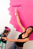 Confident Sexy Woman Paints the Walls Pink at Home