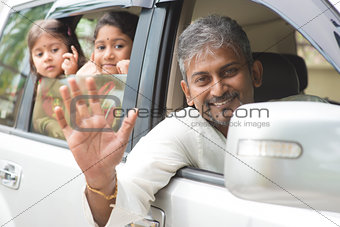 Indian family waving hands in car