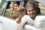 Indian man showing his new car key.
