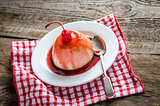 Panna cotta with berry sauce and maraschino cherry
