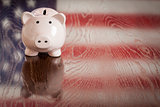 Piggy Bank with an American Flag Reflection on Table
