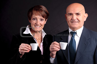 an elderly couple holding up two cups of espreso coffee