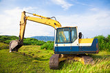excavator on the meadow with sky and ocean background