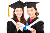two smiling young graduate students holding a diploma