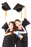 two happy young graduate students holding hats and diploma