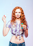 Beautiful smiling redhead girl blows bubbles. Studio portrait