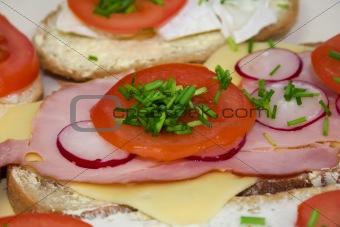 Tomato radish, ham, cheese and chive on sandwich