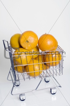 A shopping cart full of fresh whole oranges against a white background.