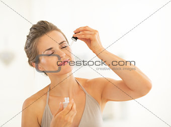 Portrait of young woman applying cosmetic elixir in bathroom