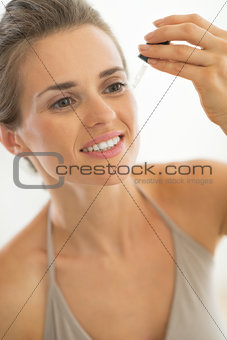 Portrait of young woman applying cosmetic elixir