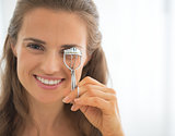 Portrait of happy young woman using eyelash curler