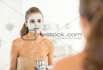 Portrait of young woman with facial cosmetic mask looking in mir