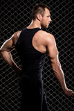 Guy showing his muscles on fence background