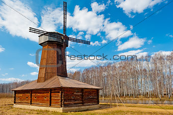 Beautiful wooden windmill in a field in spring