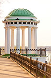 white gazebo with carved pillars on the waterfront
