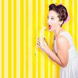 Retro pinup girl eating banana in 1950s fashion