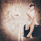 Young hitchhiking pin-up woman on vintage suitcase