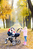 little girl with a pram on walk in autumnal alley
