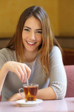 Happy woman in a coffee shop with a cup of tea