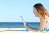 Teenager girl browsing social media in a tablet on the beach