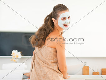 Smiling young woman wearing facial cosmetic mask