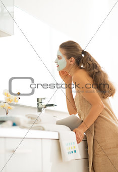 Young woman wearing facial cosmetic mask in bathroom looking in