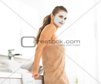 Portrait of happy young woman wearing facial cosmetic mask
